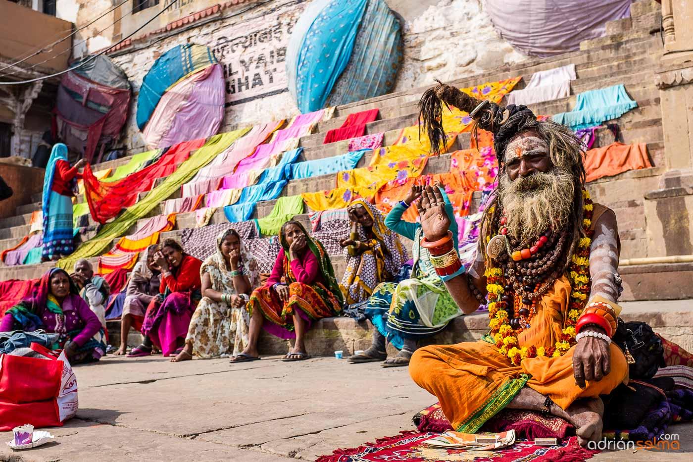 Baba en primer plano y mujeres esperando que sequen las sábanas. Varanassi